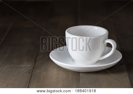white cup of coffee on brown wood table dark tone
