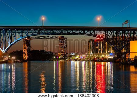 CLEVELAND OH - JUNE 17 2016: The east bank of the Cuyahoga under highway and railroad bridges glows with the lights of a new vibrant entertainment district.