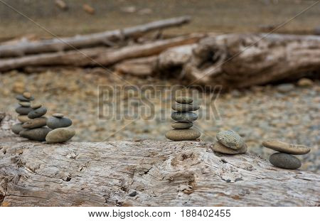 Small piles of stacked stones on a driftwood log at Ruby Beach on Washingtons Pacific Coast