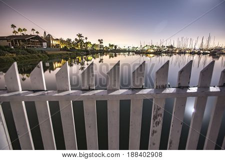 A white fence spans the water in Point Loma