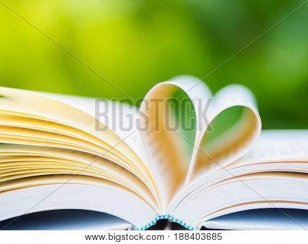 book on table in garden with top one opened and pages forming heart shape