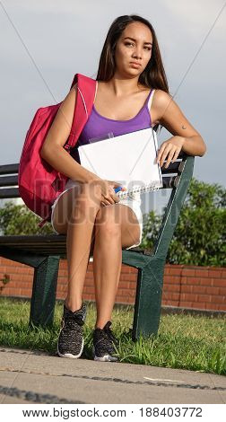 Beautiful Teenager Student Sitting on a Park Bench