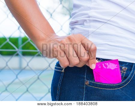 Hand holding condom in the blue jeans selective focus save sex concept.