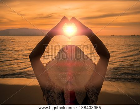 young girl holding hands in heart shape framing setting sun at sunset on ocean beach