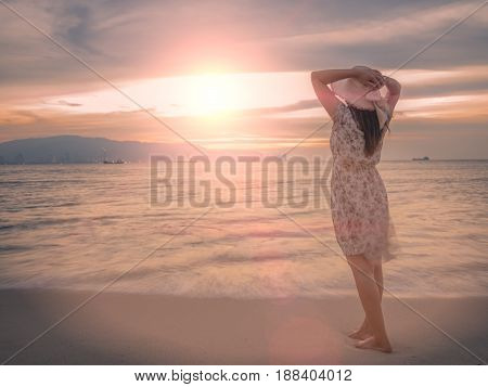 Lonely and depressed woman holding a hat and standing in front of the sea in a deserted beach on an Autumn day.
