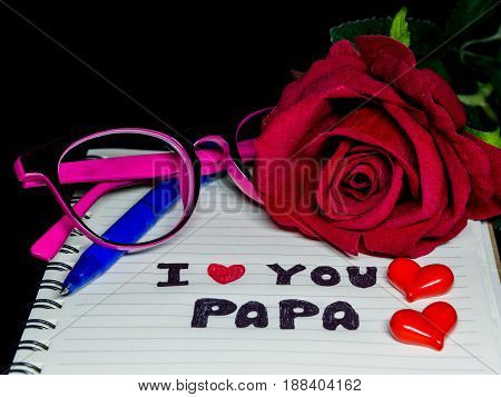 Father's day concept. I LOVE PAPA message write on note book with red rose glasses and two red hearts on dark background