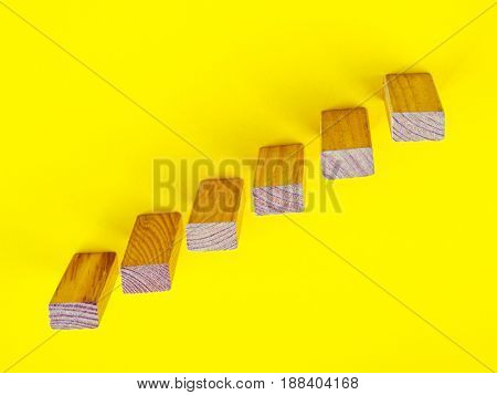 Concept of building success foundation. wooden blocks in the shape of a staircase on yellow background