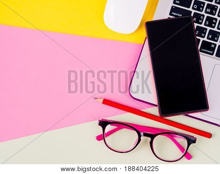 Top view of smartphone on laptop mouse glasses and pencil on pink yellow and green and yellow background