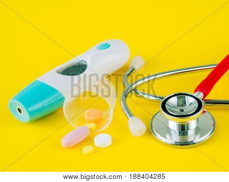 Stethoscope and pills with an electronic thermometer on yellow background Healthcare and medical concept