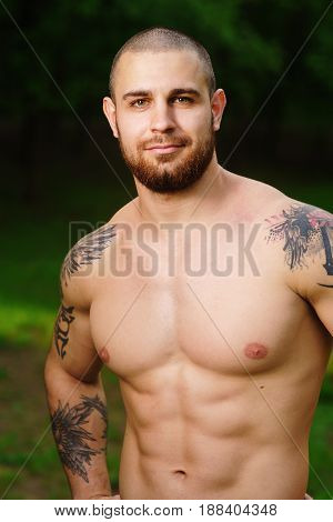 Portrait of a happy sports man standing near sea outdoors