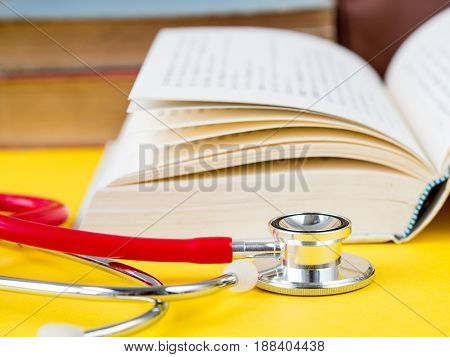 Stack of books and a stethoscope on yellow table background
