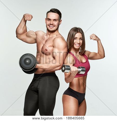 Cheerful athletic man and woman with dumbbells showing their biceps