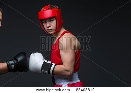 Teenage boxer in red form and helmet ready for fight. White gloves. Studio shot on black background. Copy space.