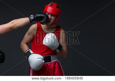 Teenage boxer in red form and helmet getting punched into face. Studio shot on black background. Copy space.