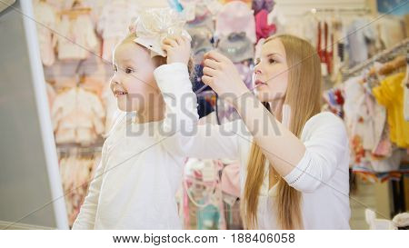 Cute girl tries on a beige bow in front of the mirror in the children's clothing store