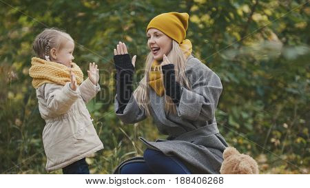 Woman with daughter little girl plays in autumn park, telephoto