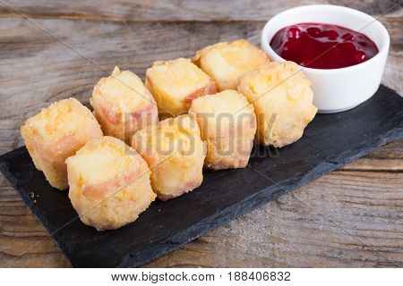 Fried cheese and bacon served on a wooden board