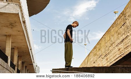 Young man preparing to jump. Parkour in the urban space. Sports in the city. Sport activity.
