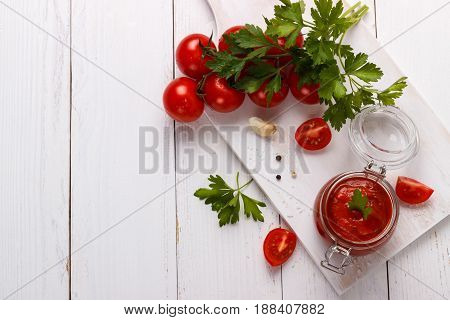 tomato sauce with garlic parsley, black and white pepper in a white bowl closeup.horizontal top view