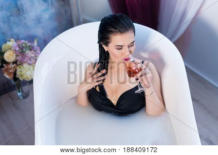 Sexy brunette woman relaxing in a hot bath with flowers and drinking champagne . she is wearing black sexual lingerie