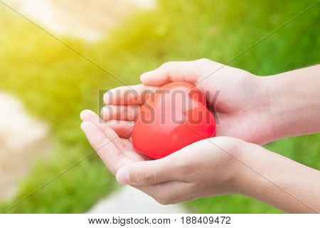 Teen hand's holding red heart ball in nature background care and valentine concept.