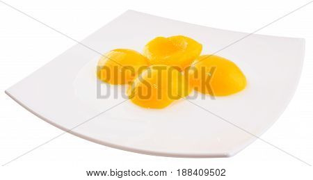 Apricot peeled halves with sugar syrup on plate isolated on white background
