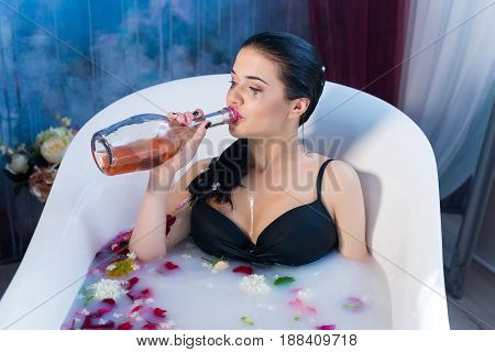 Sexy brunette drunk girl in a hot bath wearing black sexual lingerie. She is drinking champagne straight from the bottle alone. break up in a relationship concept.