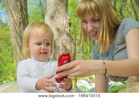 Mom on a sunny day playing with his daughter in a green park, joyful emotions baby
