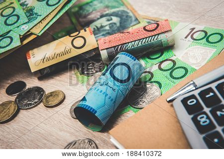 Money Australian dollars (AUD) with notebook and calculator on the table - financial and investment concepts