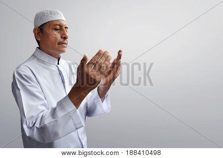 Old muslim man praying to god with hope