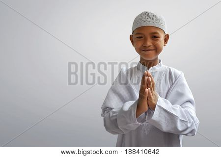 Little asian muslim kid smiling and greeting