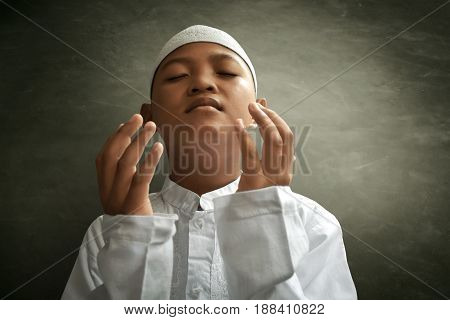 Asian muslim kid praying to god with hope