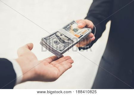 Businessman giving (or paying) money to a man US dollar bills - bribery loan and financial concepts