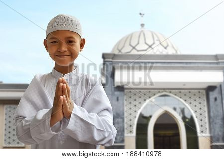 Asian muslim kid smiling and greeting outside mosque