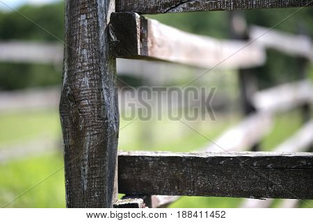 Old wooden rural corral fence in meadow against green natural background
