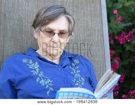 Portrait of an elder woman reading a book at her home garden