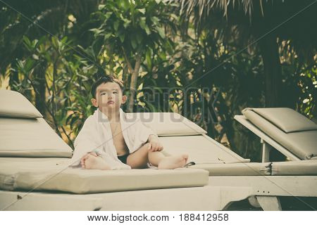 Asian Boy With White Towel Resting On A Lounge Deck Chair Or Sun Lounger Near Swimming Pool, Vintage
