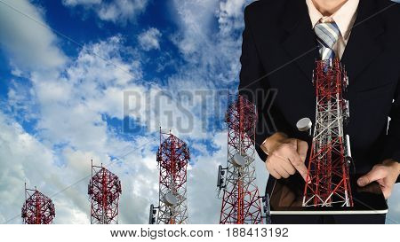 Double Exposure Of Businessman Using Tablet On Blue Sky And Telecommunication Tower Background.