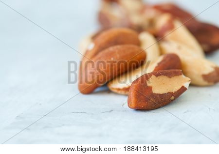 Close Up Of Brasil Nuts In A Wooden Plate On White Background. Copy Space.