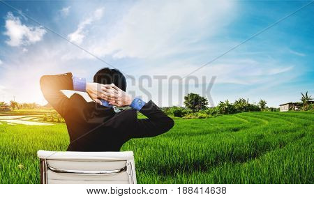 Businessman stretching arm for relax with rural scene grass field view and sunlight background