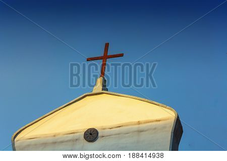 Front view of a mediterranean church on the roof of a cross.