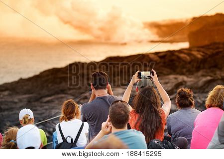Tourists Taking Photos At Kalapana Lava Viewing Area. Lava Pouring Into The Ocean Creating A Huge Po