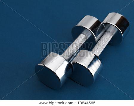 Shiny chrome plated fitness dumbbells isolated on blue background