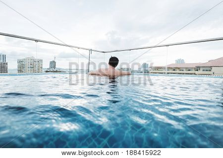 a guy relaxing in swimming pool on hotel rooftop, with city view background