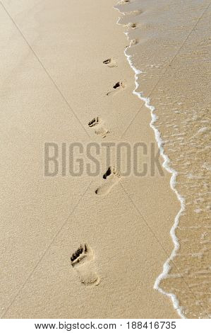 Footprints and wave in the sand on tropical beach
