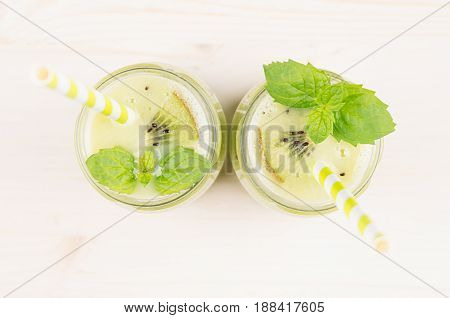 Freshly blended green kiwi fruit smoothie in glass jars with straw mint leaf top view. White wooden board background copy space.