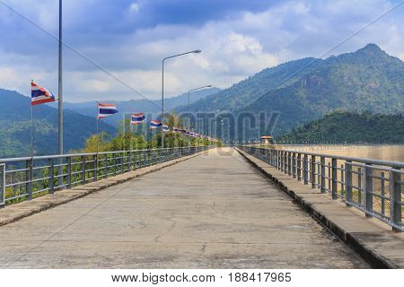 Perspective view of a long road dam with Thai national flags along the road mountain and clear blue sky background.
