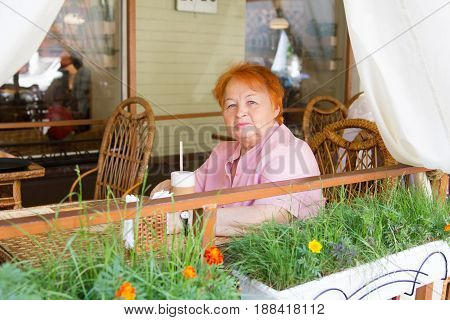 Elegantly dressed elderly woman sitting in cafe in the afternoon. Summer. City.