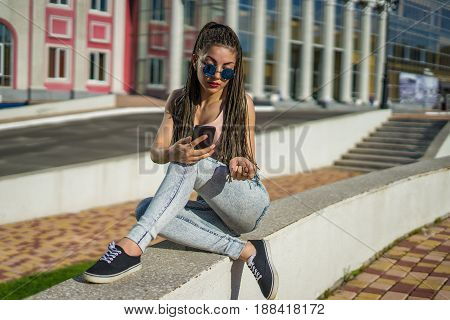 beautiful girl with zizi cornrows dreadlocks chatting on her smartphone. Urban street style
