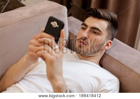 Handsome young man lying on the sofa and looking at the phone screen.